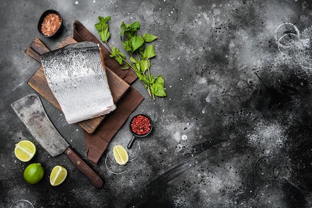 Zestaw cięcia łososia, na czarnym tle ciemnego kamiennego stołu, widok z góry płasko leżący, z miejscem na kopię tekstu
