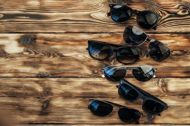 Zestaw ciemnych okularów przeciwsłonecznych na grunge brązowej powierzchni drewnianej