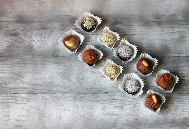 Zestaw cukierków czekoladowych. ekskluzywne ręcznie robione bonbons na drewnianym stole. widok z góry, copyspace