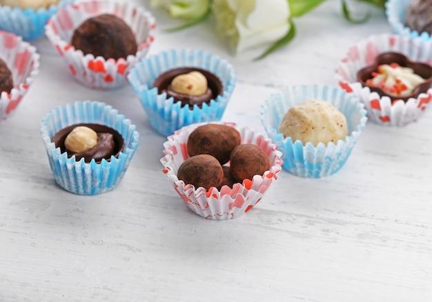 Zestaw cukierków czekoladowych z kwiatami na jasnym drewnianym tle