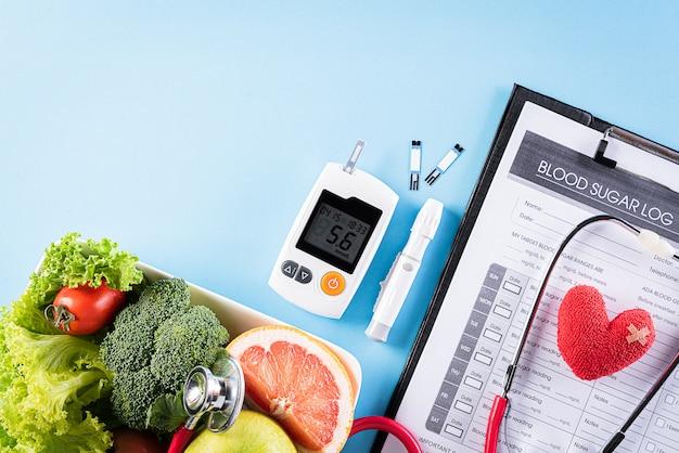 Zestaw cukrzycy i zdrowe jedzenie na niebieską ścianą.
