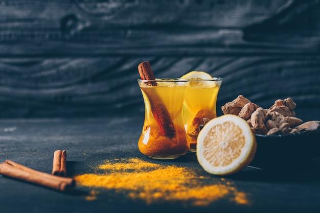 Zestaw cytryny, imbiru i suchego cynamonu i imbiru w proszku w filiżankach herbaty na ciemnym tle z teksturą. widok z boku. miejsce na tekst