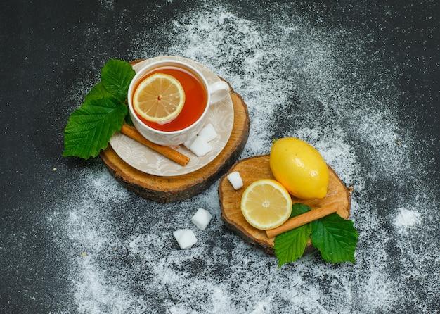 Zestaw cytryny, suchego cynamonu, kostek cukru i filiżanki herbaty na kawałkach drewna i ciemności. wysoki kąt widzenia.