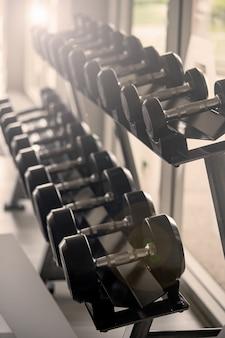 Zestaw czarnych hantli. zamyka w górę wiele metali dumbbells na stojaku w sport sprawności fizycznej centrum