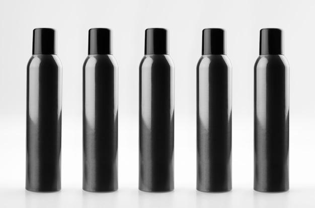 Zestaw czarnych, kosmetycznych puszek aerozolu z aluminium z nakrętkami. butelki kosmetyczne z lakierem do włosów.