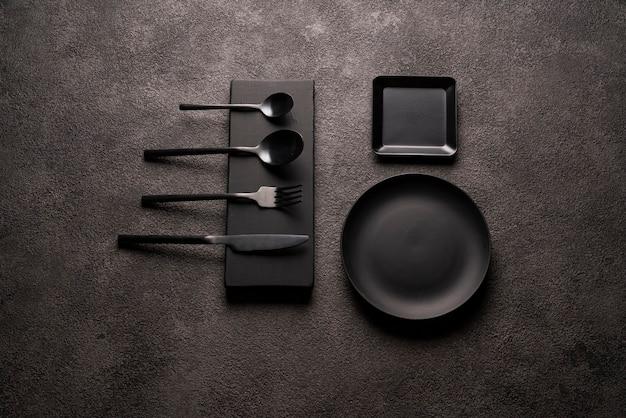 Zestaw czarnych matowych naczyń do jadalni - widelec, łyżka, nóż i zestaw talerzy. mieszkanie leżało martwa na betonowym tle. koncepcja kuchni lub restauracji