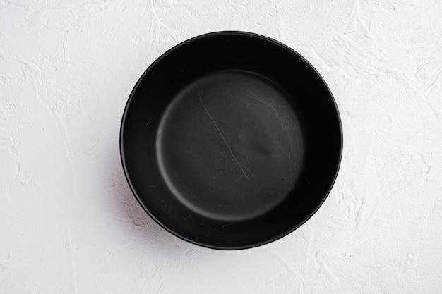 Zestaw czarnych misek, z kopią miejsca na tekst lub jedzenie, z kopią miejsca na tekst lub jedzenie, widok z góry płaski, na białym tle kamiennego stołu