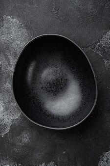 Zestaw czarnych misek, z kopią miejsca na tekst lub jedzenie, z kopią miejsca na tekst lub jedzenie, widok z góry płaski, na czarnym ciemnym tle kamiennego stołu