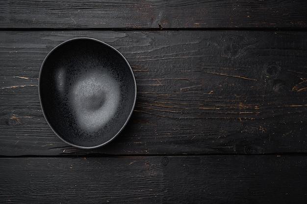 Zestaw czarnych misek, z kopią miejsca na tekst lub jedzenie, z kopią miejsca na tekst lub jedzenie, widok z góry płasko leżał, na tle czarnego drewnianego stołu