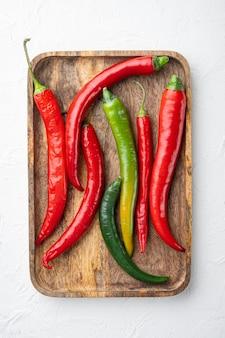 Zestaw czerwonej i zielonej papryczki chili, na drewnianej tacy, na białym tle, widok z góry płaski lay