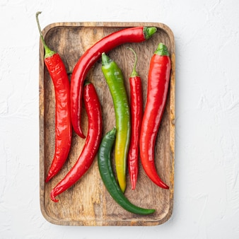 Zestaw czerwonej i zielonej papryki chili, na drewnianej tacy, na białym tle, płaski widok z góry