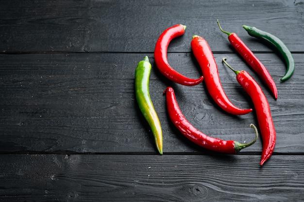 Zestaw czerwonej i zielonej papryki chili, na tle czarny drewniany stół, z copyspace i miejsca na tekst