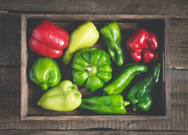 Zestaw czerwonej i zielonej papryki o różnych kształtach. pełna taca na warzywa.