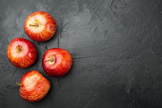 Zestaw czerwonych jabłek, na tle czarnego ciemnego kamiennego stołu, płaski widok z góry, z miejscem na kopię tekstu