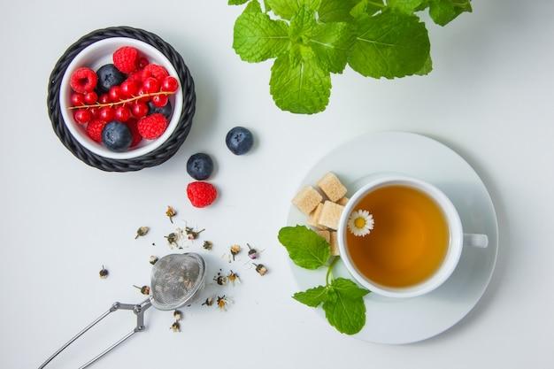 Zestaw czerwonych porzeczek, rumianku, ziół, cukru, liści mięty oraz jagód i malin w misce.