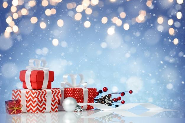 Zestaw czerwonych prezentów świątecznych na niebiesko ze złotymi światłami