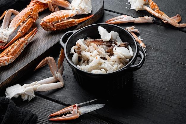 Zestaw części gotowanego mięsa tajskiego kraba niebieski pływanie, na tle czarny drewniany stół