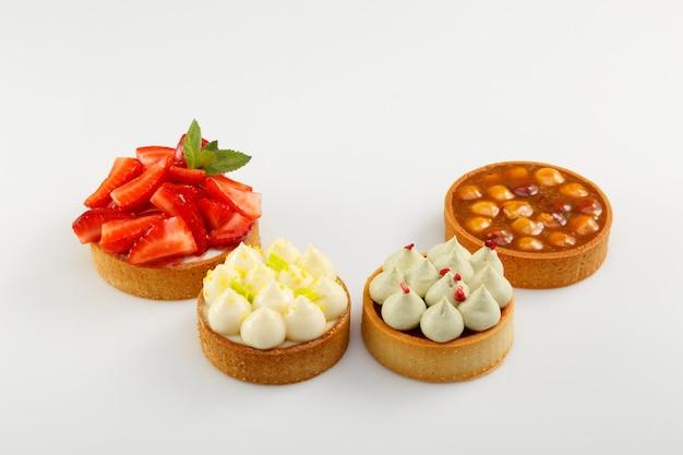 Zestaw czterech mini tart z jagodami malin, śmietaną i orzechami laskowymi