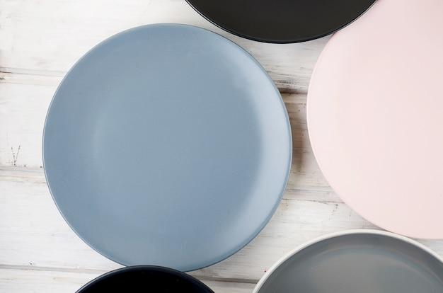 Zestaw czystej zastawy stołowej w pastelowym kolorze na drewnianym stole