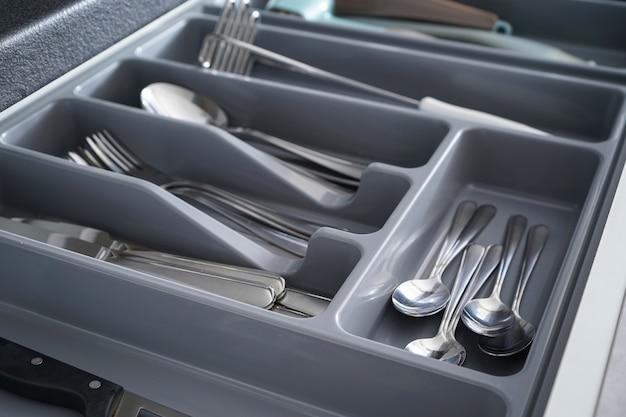 Zestaw czystych przyborów kuchennych w szufladzie, zbliżenie.
