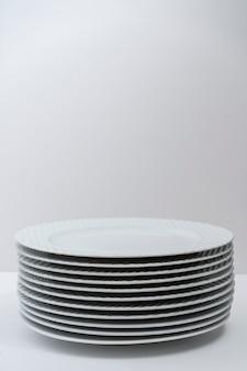 Zestaw czystych ułożonych białych talerzy na białym stole. skopiuj miejsce