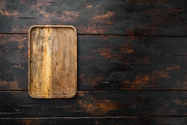Zestaw desek do krojenia lub serwowania wiosła, płaski widok z góry, z miejscem na kopię tekstu lub produktu, na starym ciemnym tle drewnianego stołu