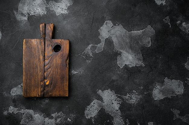 Zestaw desek do krojenia z drewna sosnowego, na czarnym tle ciemnego kamiennego stołu, widok z góry na płasko, z miejscem na kopię tekstu lub produktu