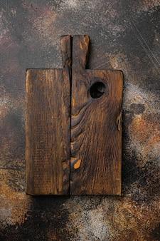 Zestaw deski do krojenia w wieku, widok z góry płasko leżący, z miejscem na kopię tekstu lub jedzenia, na starym ciemnym tle rustykalnym stołu