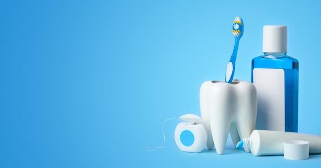 Zestaw do czyszczenia zębów i jamy ustnej. pasta do zębów, szczoteczka do zębów, nici dentystyczne i płyn do płukania jamy ustnej na niebieskim tle.
