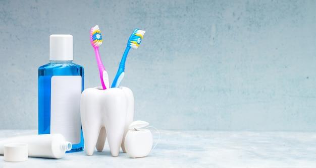 Zestaw do czyszczenia zębów i jamy ustnej. pasta do zębów, szczoteczka do zębów, nici dentystyczne i płyn do płukania jamy ustnej na szarym tle.