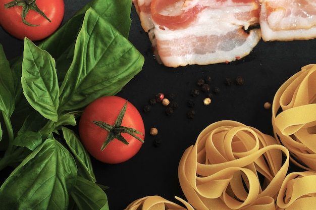 Zestaw do gotowania makaronu z gniazdami makaronu, boczkiem, liśćmi bazylii i pomidorem