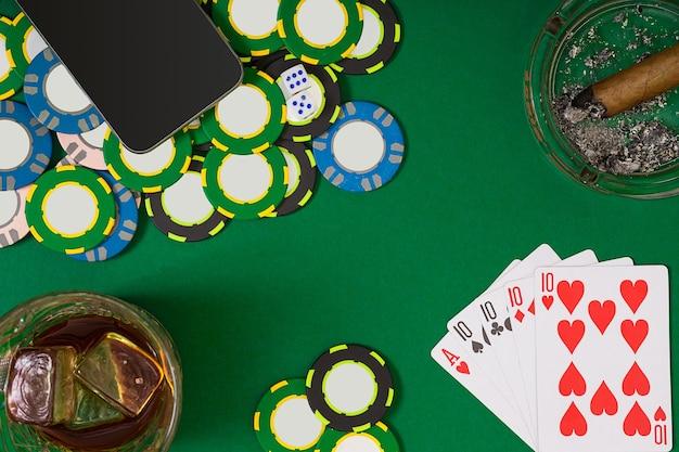 Zestaw do gry w pokera z kartami i żetonami na zielonym stole. widok z góry z miejscem na kopię. makieta układu szablonu transparentu dla kasyna online. zielony stół, widok z góry na miejsce pracy.