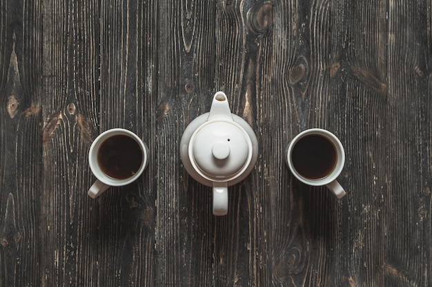 Zestaw do herbaty dla pary. filiżanki i teapot na czarnym wieśniaka stole.