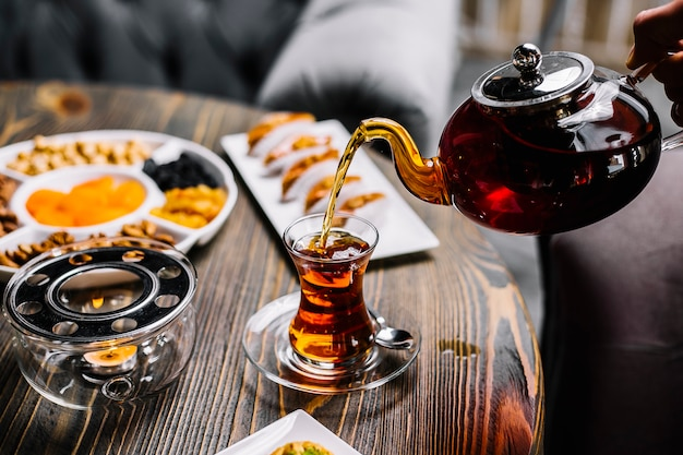 Zestaw do herbaty pakhlava suszone owoce orzechy dzbanek do herbaty i widok z boku szkło narodowe