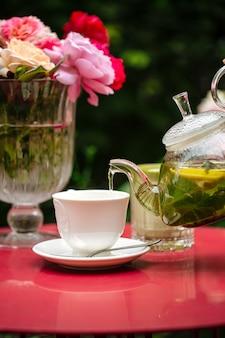 Zestaw do herbaty w ogrodzie na stole ozdobionym kwiatami