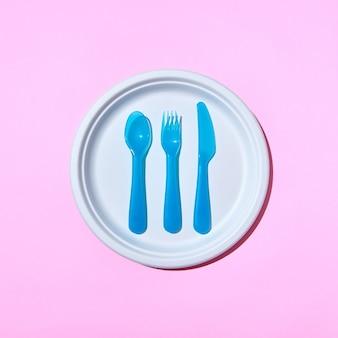 Zestaw do jadalni plastikowych sztućców na białym talerzu na różowym pastelowym tle z miejscem na kopię. leżał na płasko.
