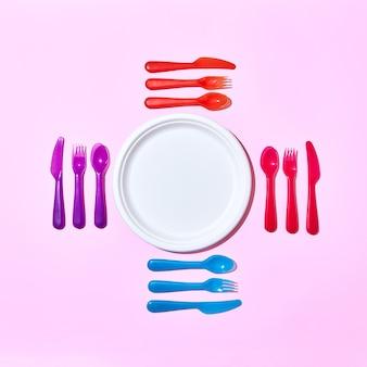 Zestaw do jedzenia z jednorazowych plastikowych sztućców, serwujący wokół papierowego białego talerza na pastelowym różowym tle z miejscem na kopię. leżał na płasko.
