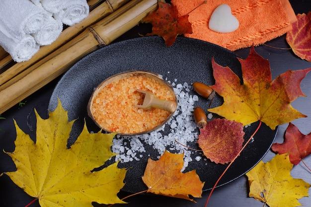 Zestaw do jesiennego zabiegu spa z dekoracją z opadłych liści, pomarańczowym ręcznikiem, bambusową i pomarańczową solą do kąpieli