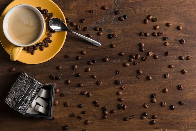 Zestaw do kawy i cukiernica w pobliżu ziaren kawy