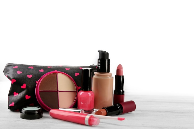 Zestaw do makijażu z kosmetyczką i kosmetykami na białym drewnianym