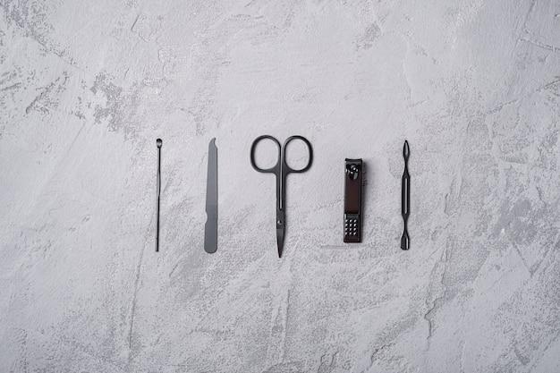 Zestaw do manicure, pedicure i akcesoriów w rzędzie, kamień, beton, widok z góry