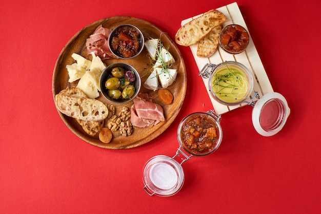 Zestaw do masła dyniowego w szklanym słoju. odmiana sera, oliwki, prosciutto, pieczone plastry bagietki, selektywne focus, kwadratowa uprawa.