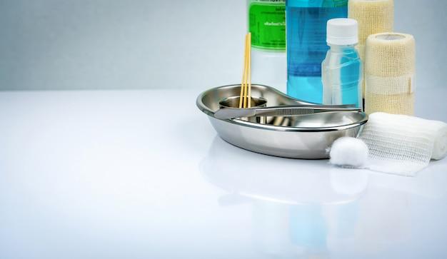 Zestaw do opatrywania ran i płyta ze stali nierdzewnej, kleszcze, butelka alkoholu, elastyczny bandaż, bawełniana kulka, pojemnik do chirurgii. zaopatrzenie medyczne.