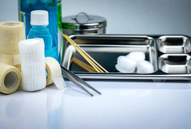 Zestaw do opatrywania ran i płyta ze stali nierdzewnej, kleszcze, kubek z jodem, bandaż dopasowany, elastyczny bandaż zatrzymujący, antyseptyczna i zwykła butelka z solą fizjologiczną.