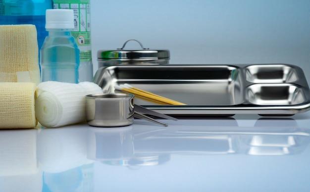 Zestaw do opatrywania ran i płyta ze stali nierdzewnej, szczypce, kubek z jodem, bandaż dopasowany, elastyczny bandaż zatrzymujący, antyseptyczna i normalna butelka z solą fizjologiczną, pojemnik na instrumenty. zaopatrzenie medyczne.