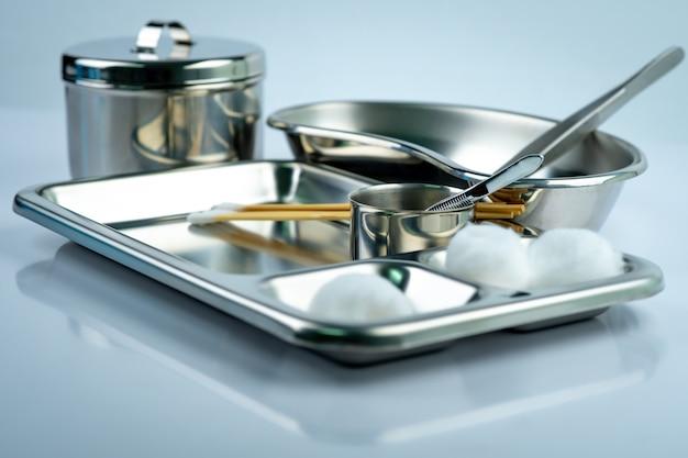 Zestaw do opatrywania ran na płytce ze stali nierdzewnej. biała bawełniana kulka, patyczek, szczypce, miska nerkowa, kubek z jodem, pojemnik na instrumenty z pokrywką lub zestaw słoików ze stali nierdzewnej. narzędzia medyczne.