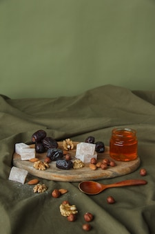 Zestaw do picia herbaty. różne słodycze, orzechy i miód na herbatę na drewnianej desce do krojenia. orzechy włoskie, migdały, orzechy laskowe, daktyle, rahatlukum, miód, suszone owoce. zdrowe słodycze, naturalne słodycze.
