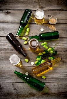 Zestaw do piwa. butelki i szklanki piwa, słodu i zielonego chmielu na drewnianym stole. widok z góry