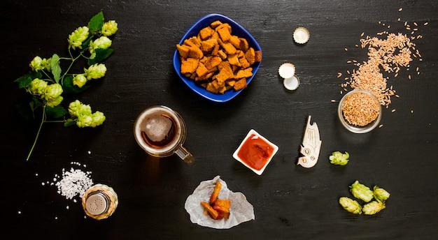 Zestaw do piwa. szklanka piwa, krakersy, keczup, sól. składniki do warzenia: słód i chmiel na drewnianym czarnym stole.