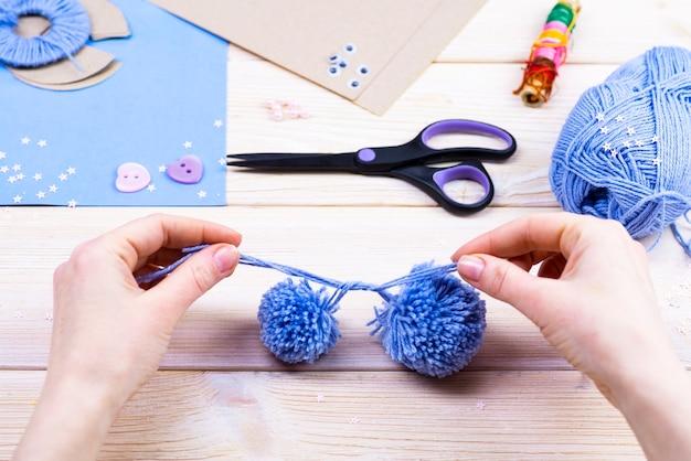 Zestaw do robótek ręcznych na drewnianym stole. nici, nożyczki, papier do robienia pomponów